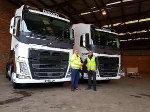 Debach Logistics Manager Lionel Scutcher with Dave Beecroft from Volvo Trucks in front of our two new trucks